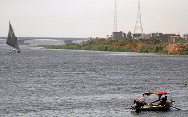 "Egyptian fishermen sail in front of the new bridge crossing the River Nile and named the ""Long Live Egypt"" bridge, part of Rod al-Faraj Axis project, near Cairo's Warraq Island"