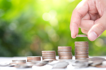 Closeup hand putting growing coins stacking with greenery background and sunlight. Saving  investment and profit concept.-Image.