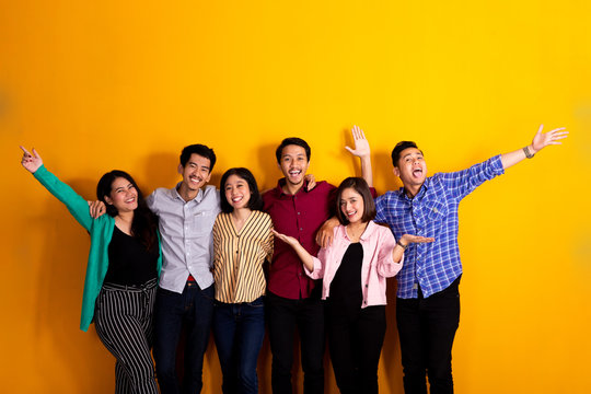 happy young asian friend raised their arm together over yellow background