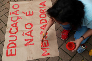 "Students prepare a poster thatÊreads, ""Education is not merchandise"" before a protest in Sao Paulo"