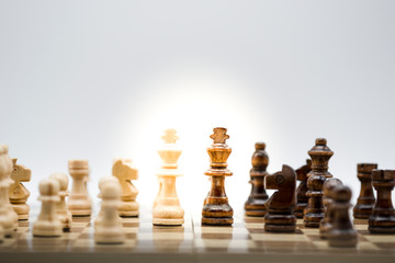 Face to face of wooden black and white chess on chess board with sunlight. Battle in game and business concept.