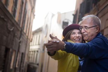 coppia di anziani balla felice in mezzo a una strada
