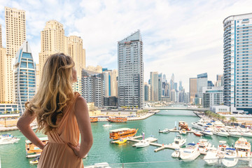Foto auf Gartenposter Dubai Woman in Dubai Marina, United Arab Emirates. Attractive lady wearing a long dress admiring Marina daylight views