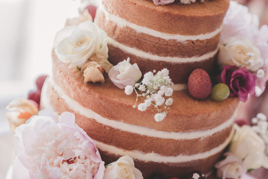 Naked wedding cake with fruit and flowers