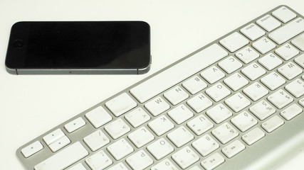 Wall Mural - keyboard with smart phone on white background
