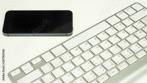 Wall mural keyboard with smart phone on white background