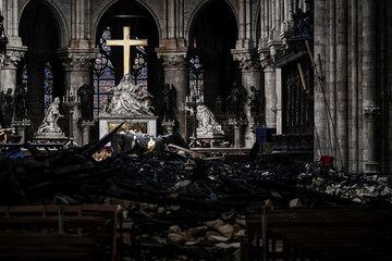 A picture shows rubbles and the cross at the altar, inside the the Notre-Dame Cathedral after it sustained major fire damage from the previous month, during the visit of Canadian Prime Minister in Notre-Dame Cathedral in Paris