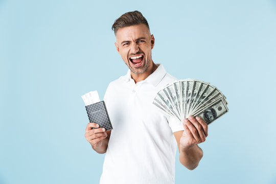 Handsome excited emotional adult man posing isolated over blue wall background holding passport with tickets and money.