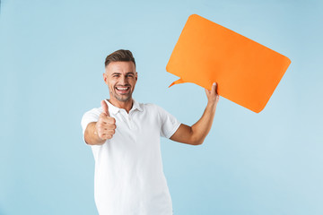 Excited emotional adult man posing isolated over blue wall background holding speech bubble.
