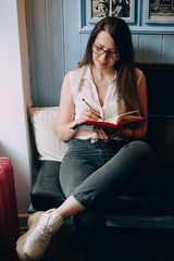 Stylish young hipster woman with notepad in cafe. Writes and ponders new ideas.