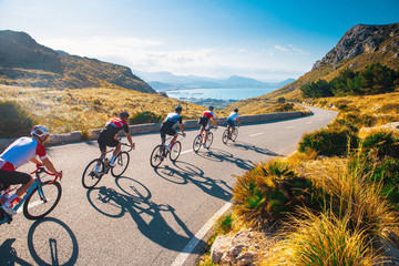 Group of cyclist ride together on road bicycles in beautiful nature. Sunset light, sea in background. Wall mural