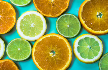 horizontal view of slices of citrus fruit on a bright high contrast turquoise background Wall mural