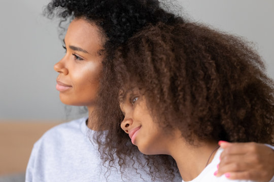 Close up young African American mother hugging teen daughter