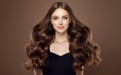 Beauty girl with long  and   shiny wavy hair .  Beautiful   woman model with curly hairstyle . Wall mural