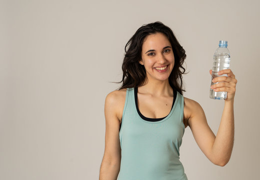 Healthy attractive sport woman holding and drinking water bottle in healthy lifestyle concept