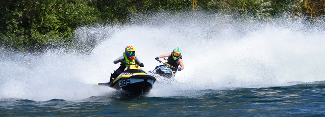 Tuinposter Water Motor sporten Jet Ski Racers in competitive event on lake making a lot of spray.