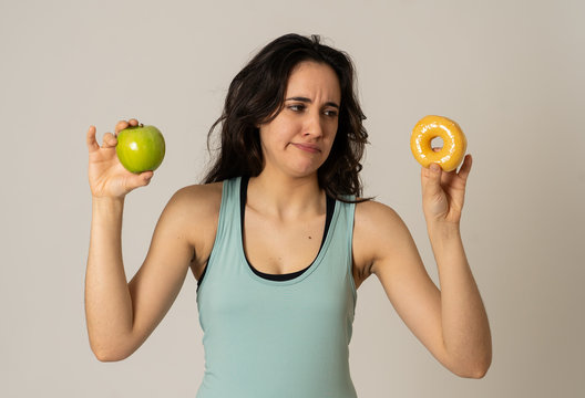 Attractive young woman on a diet deciding between an apple and a doughnut