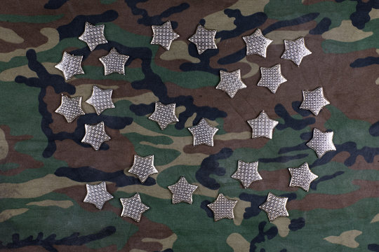 gold stars on military camouflage fabric