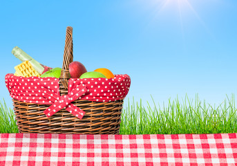 a picnic table covered with checkered tablecloth and picnic basket