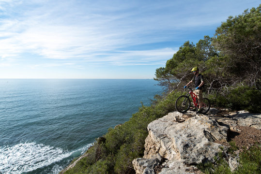 Mountainbiker standing on top of the rocks, looks out across sea.