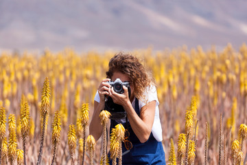 Girl taking picture with film camera in aloe vera field, Fuerteventura
