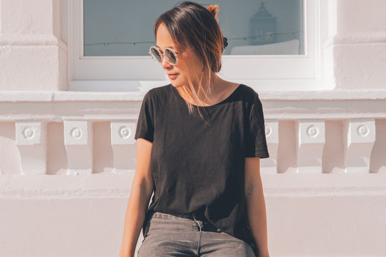 Asian woman wearing sunglasses on a sunny day with jeans and a t-shirt