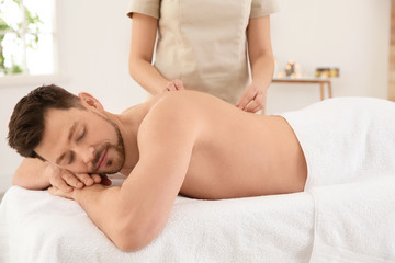 Handsome man receiving back massage in spa salon