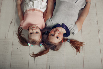 Two sisters girls have a fun on the floor portrait