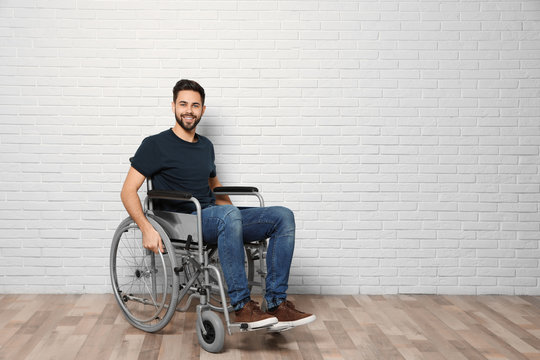 Young man in wheelchair near brick wall indoors. Space for text