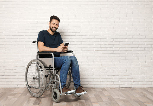 Young man with smartphone in wheelchair near brick wall indoors. Space for text