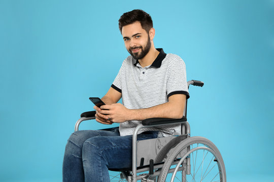 Young man with smartphone in wheelchair on color background