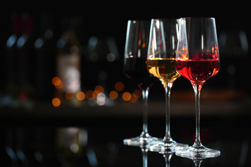 Papiers peints Alcool Row of glasses with different wines on bar counter against blurred background. Space for text