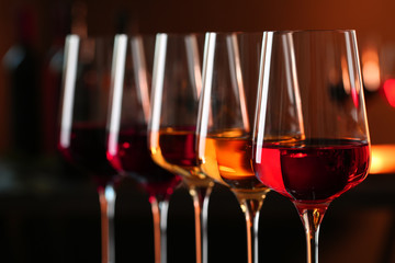 Poster Wine Row of glasses with different wines against blurred background, closeup