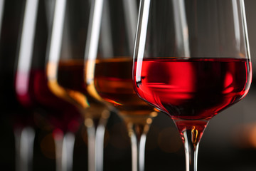 Poster Vin Row of glasses with different wines on blurred background, closeup
