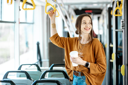 Young and happy passenger enjoying trip at the public transport, standing with coffee in the modern tram