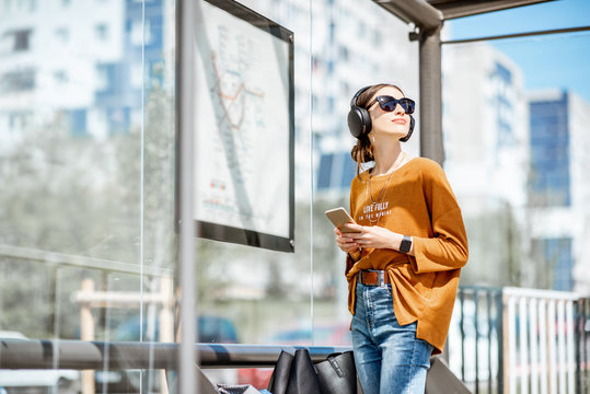 Young stylish woman waiting for the public transport while standing at the modern tram station outdoors