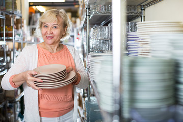 consumer woman choosing plates for kitchen