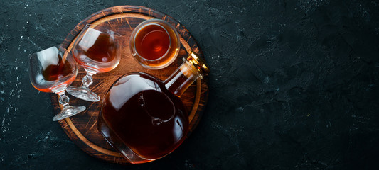 A bottle of cognac and glasses on a black background. Brandy. Top view. Free space for your text. Fototapete