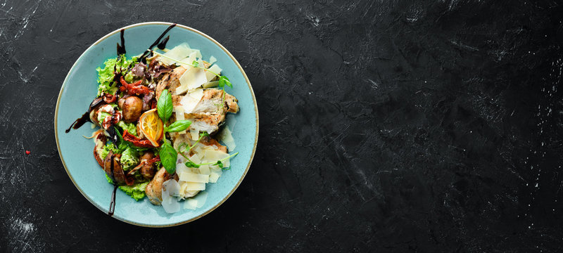 Salad with chicken, grilled vegetables and parmesan. In the plate. Rustic style. Top view. Free space for your text.