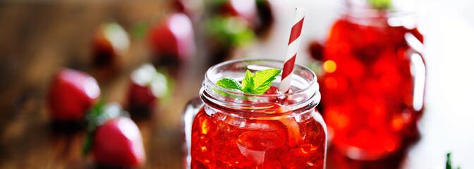 strawberry cocktail in mason jar with mint garnish panorama