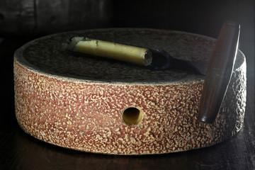 organic hay milk cheese wheel from German Allgäu region with grading iron in ripening storage