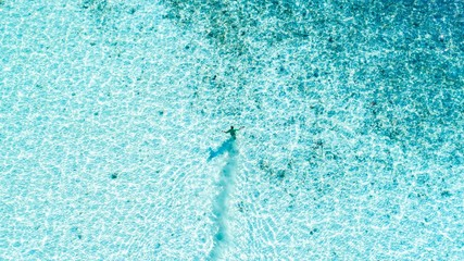 aerial photo of person swimming on body of water during daytime