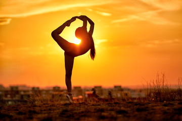 ballerina standing with her one foot during sunset