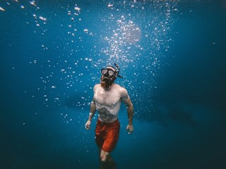 man snorkeling under body of water