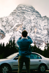 man standing near gray sedan taking picture of snow-covered mountain