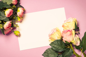 Empty paper sheet and flowers on pink background.