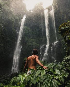 naked man near waterfall during daytime