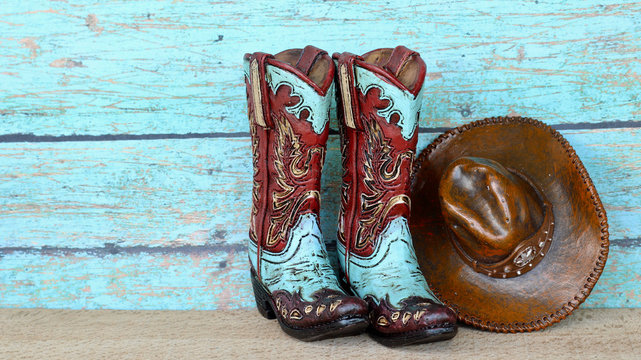 pair of colorful blue and red cowboy boots and hat standing on a natural wood with a blue wooden background