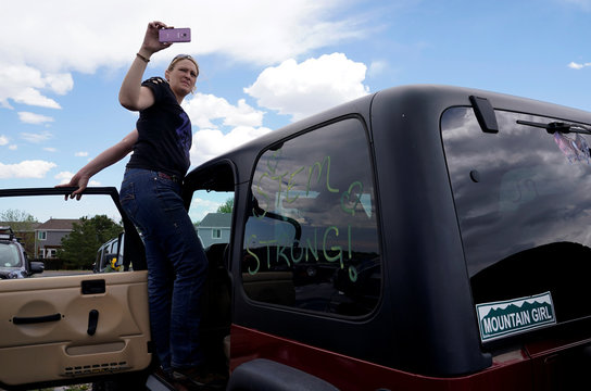 A woman takes a photo standing on her Jeep that was part of a convoy for the memorial service of the shooting victim Kendrick Castillo of the Science, Technology, Engineering and Math (STEM) School in Highlands Ranch