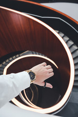 person wearing gold-colored watch near spiral staircase